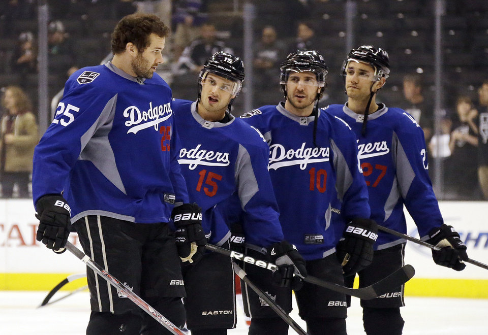 Photo - From left, Los Angeles Kings left wing Dustin Penner (25), center Brad Richardson (15), center Mike Richards (10) and defenseman Alec Martinez (27) warm up wearing Los Angeles Dodgers jerseys before an NHL hockey game against the Columbus Blue Jackets in Los Angeles, Thursday, April 18, 2013. (AP Photo/Reed Saxon)