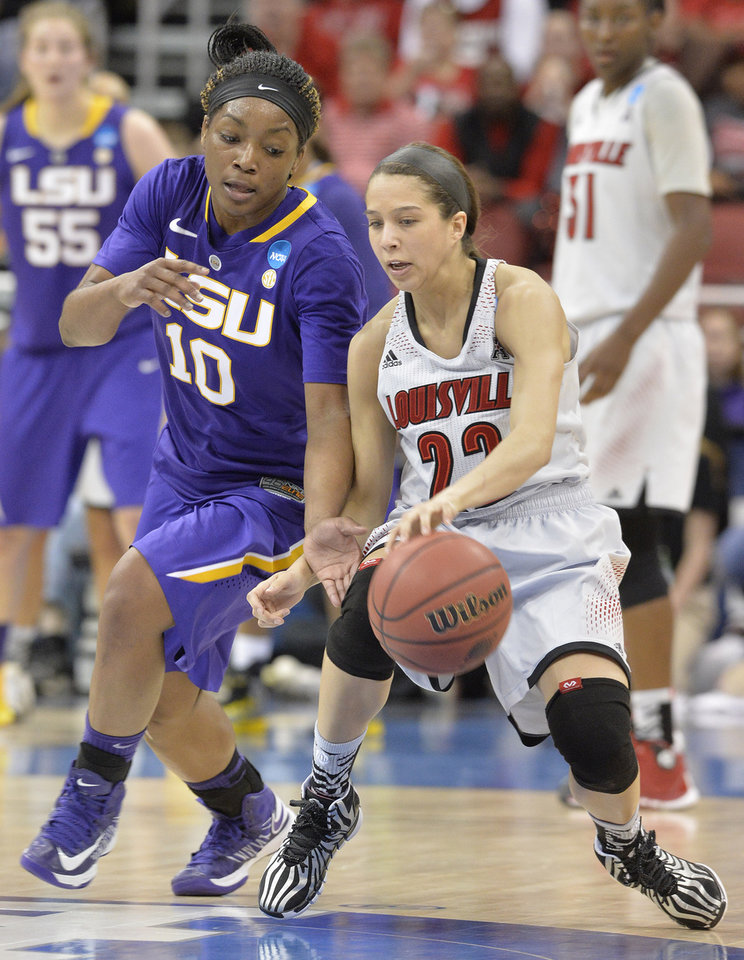 Photo - LSU's Jasmine Rhodes, left, attempts to steal the ball from Louisville's Jude Schimmel during the first half in a regional semifinal game at the NCAA women's college basketball tournament on Sunday, March 30, 2014, in Louisville, Ky. (AP Photo/Timothy D. Easley)