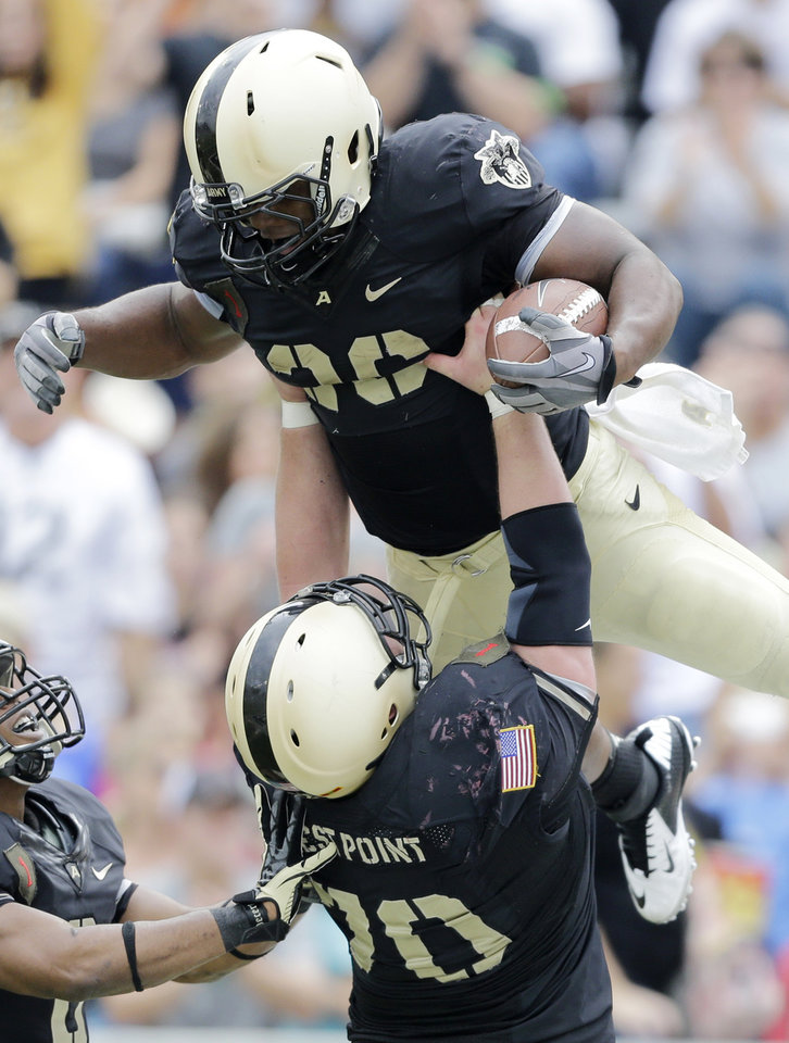 Photo -   Army running back Larry Dixon (26) celebrates a touchdown with teammate Stephen Shumaker (70) during the second half of an NCAA college football game against Boston College on Saturday, Oct. 6, 2012, in West Point, N.Y. Army won, 34-31. (AP Photo/Mike Groll)