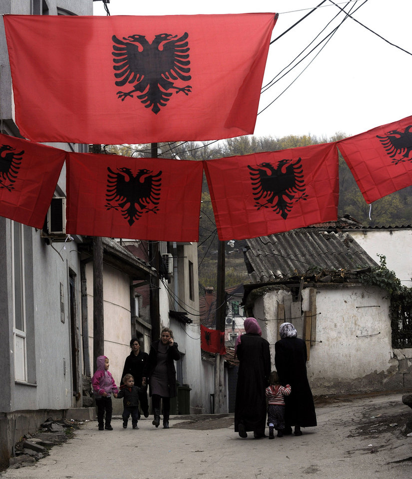 In this photo taken Friday, Nov. 23, 2012, people walk through a small street decorated with Albanian flags, in Skopje, Macedonia. Macedonian capital Skopje, particularly the parts populated with ethnic Albanians, are flooded with Albanian flags, in the eve of the celebration of 100 years of Albania's independence and the national flag. Ethnic Albanians make up a quarter of Macedonia's 2.1 million people and are the largest ethnic minority in the country. (AP Photo/Boris Grdanoski)