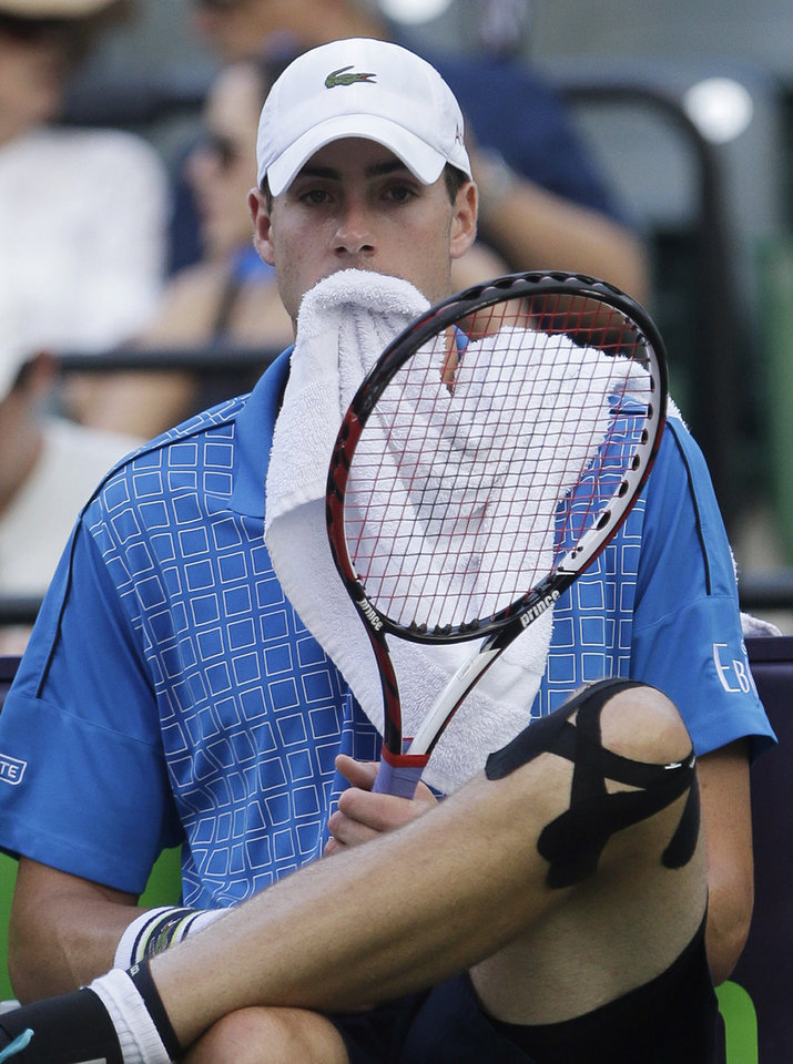 Photo - John Isner, of the United States, rests between sets during a match against Donald Young, of the United States, at the Sony Open tennis tournament, Saturday, March 22, 2014, in Key Biscayne, Fla. (AP Photo/Wilfredo Lee)