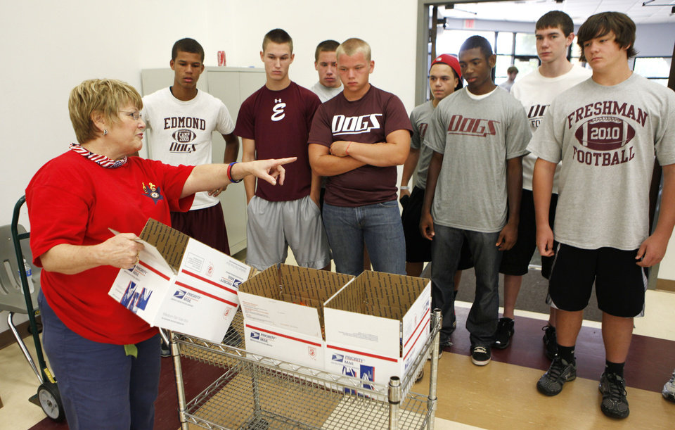 Photo - Sherry Stensrud, President of the Chapter 8 Blue Star Mothers, explains to Edmond football players how to pack care packages for deployed military, during a Blue Star Mother's event at the Peace Lutheran Church in Edmond, OK, Saturday, July 24, 2010. By Paul Hellstern, The Oklahoman