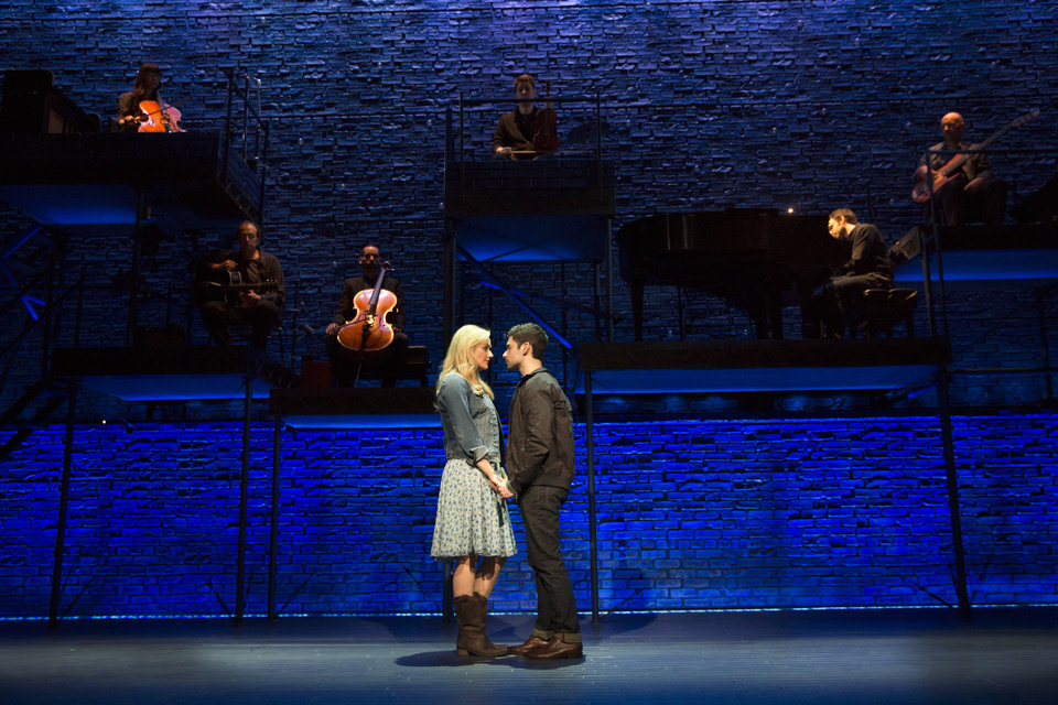 Photo - This theater image released by The Hartman group shows Adam Kantor, right, and Betsy Wolfe during a performance of