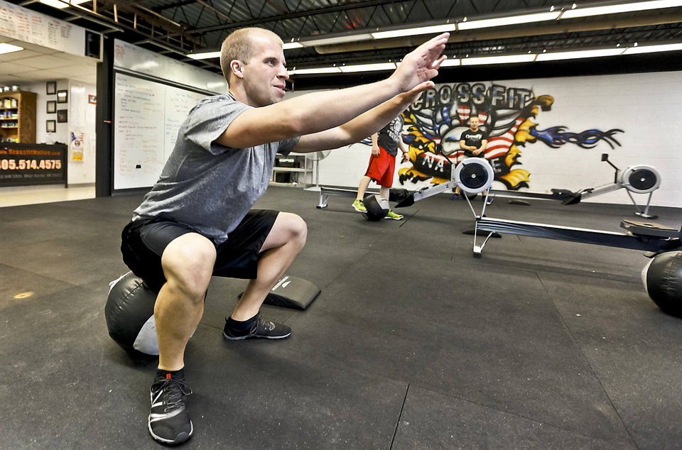 Michael Ballard does air squats as part of a workout at Crossfit Native in Warr Acres.  Photo by CHRIS LANDSBERGER, The Oklahoman