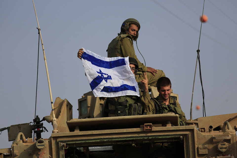Photo - Israeli soldiers display national flag on top of an armored personnel carrier near the border of  Israel and Gaza Strip Wednesday, July 23, 2014. Israeli troops battled Hamas militants on Wednesday near a southern Gaza Strip town, sending Palestinian residents fleeing, as the U.S. secretary of state presses ahead with top-gear efforts to end the conflict that has killed hundreds of Palestinians and tens of Israelis. (AP Photo/Tsafrir Abayov)