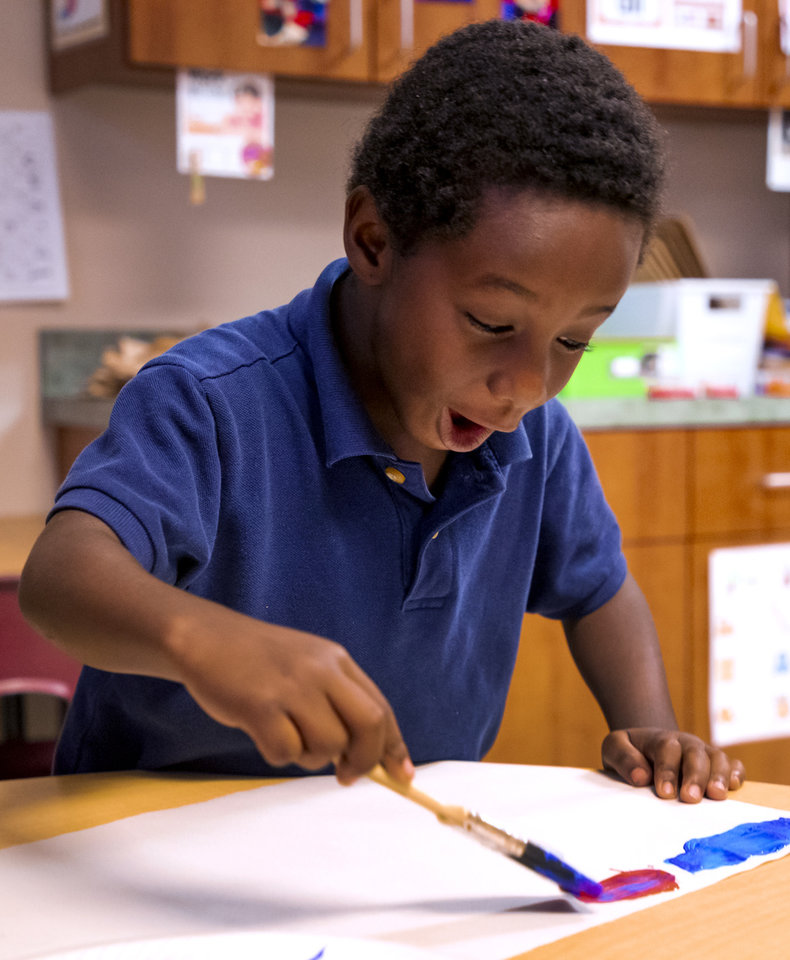 Photo - Heronville Elementary first grader Travis Edgar reacts as he begins to paint his view of a lesson from his teacher Alicia Strawn on the story of Thanksgiving from the Native American perspective while in class at Heronville Elementary in Oklahoma City, Okla. on Thursday, Nov. 21, 2019. [Chris Landsberger/The Oklahoman]