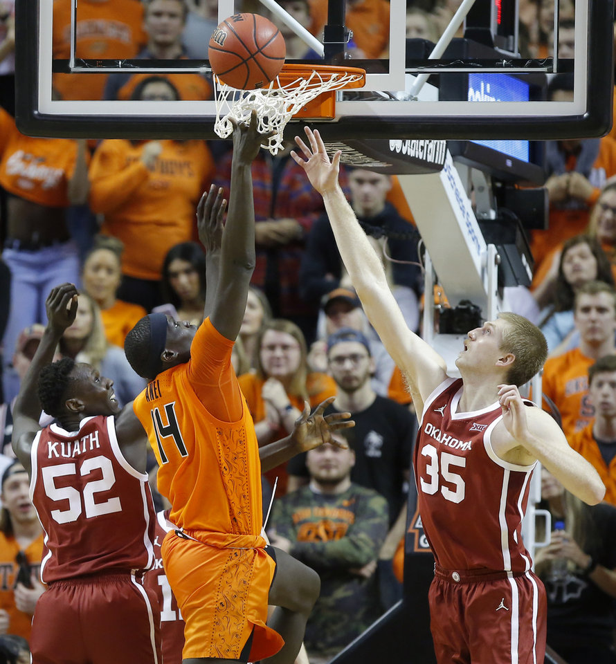 Photo - Oklahoma State's Yor Anei (14) makes a basket between Oklahoma's Kur Kuath (52) and Brady Manek (35) during an NCAA men's Bedlam basketball game between the Oklahoma State University Cowboys (OSU) and the University of Oklahoma Sooners (OU) at Gallagher-Iba Arena in Stillwater, Okla., Saturday, Feb. 22, 2020. Oklahoma State won 83-66. [Bryan Terry/The Oklahoman]