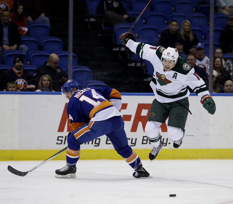 Photo - Minnesota Wild's Zach Parise, right, jumps over New York Islanders' Thomas Hickey's leg during the first period of the NHL hockey game, Tuesday, March 18, 2014, in Uniondale, New York. (AP Photo/Seth Wenig)