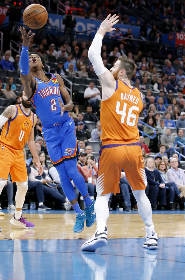 Photo - Oklahoma City's Shai Gilgeous-Alexander (2) shoots a basket as Phoenix's Aron Baynes (46) defends during the NBA basketball game between the Oklahoma City Thunder and the Phoenix Suns at the Chesapeake Energy Arena in Oklahoma City , Friday, Dec. 20, 2019.   [Sarah Phipps/The Oklahoman]