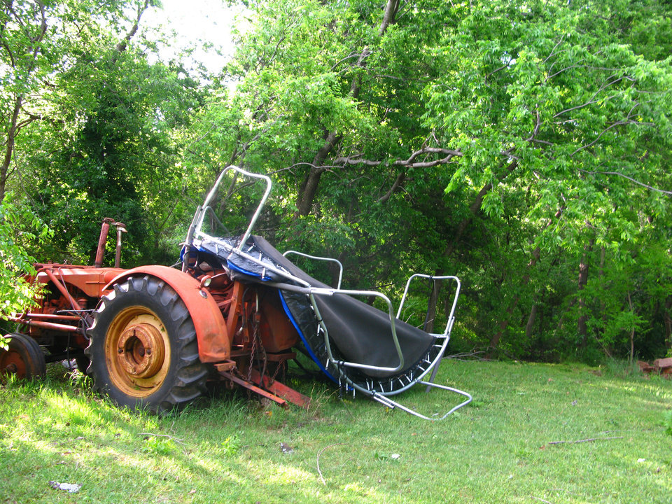 A trampoline from one of Judy Pendergraft?s neighbors is wrapped around a tractor in the Hidden Valley addition in southeast Edmond. PHOTO BY LILLIE-BETH BRINKMAN, THE OKLAHOMAN