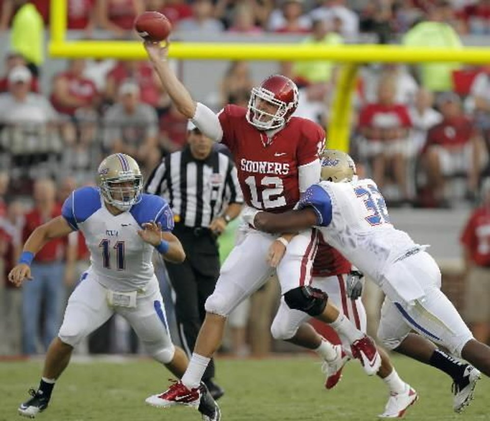 Photo - Oklahoma's Landry Jones (12) is hit by Tulsa's Curnelius Arnick (32) during the college football game between the University of Oklahoma Sooners ( OU) and the Tulsa University Hurricanes (TU) at the Gaylord Family-Memorial Stadium on Saturday, Sept. 3, 2011, in Norman, Okla. Photo by Chris Landsberger, The Oklahoman ORG XMIT: KOD