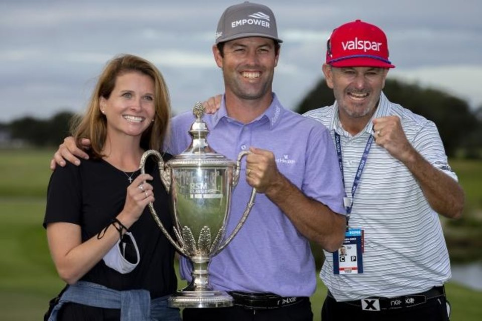 Photo -  Robert Streb, center, his wife Maggie Streb, left, and his caddie Steve Catlin, right, celebrate with the trophy after a winning a second-hole playoff against Kevin Kisner at the RSM Classic on Sunday in St. Simons Island, Ga. [AP Photo/Stephen B. Morton]