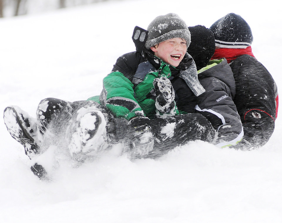 Photo - From left, Daniel Meier, 11, Matthew Thorn, 11, and Logan Smith, 12 all of Winona, Minn., share a sled while sledding down the hill at Bluffside Park Thursday, Dec. 20, 2012, in Winona, Minn. (AP Photo/Winona Daily News, Joe Ahlquist)