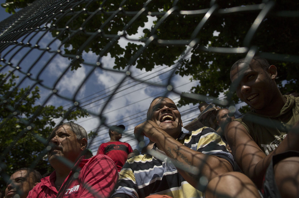 Photo - In this April 27, 2014 photo, residents watch an amateur soccer match behind a fence at the Vila da Penha neighborhood of Rio de Janeiro, Brazil. Brazil is a five-time champion of the World Cup, and will host this year's international soccer tournament starting June 12. The government says it wants to use the World Cup to convince international visitors to keep coming back to Brazil after the tournament ends. (AP Photo/Leo Correa)