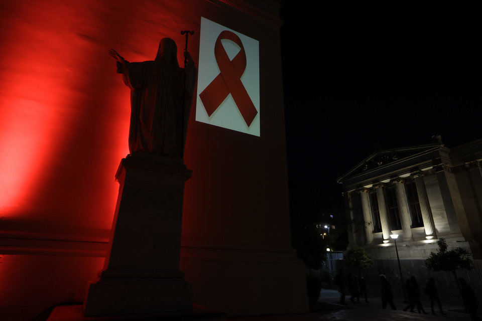 Photo - A red ribbon, the symbol of support for those living with HIV, is projected near to the statue of a Greek bishop, in front of the neoclassical facade of the old Athens University building in central Athens, lit in red to observe World AIDS Day, on Thursday, Dec. 1, 2016. Greece has recorded a 40 percent drop in new HIV infections this year, according to health officials. (AP Photo/Thanassis Stavrakis)