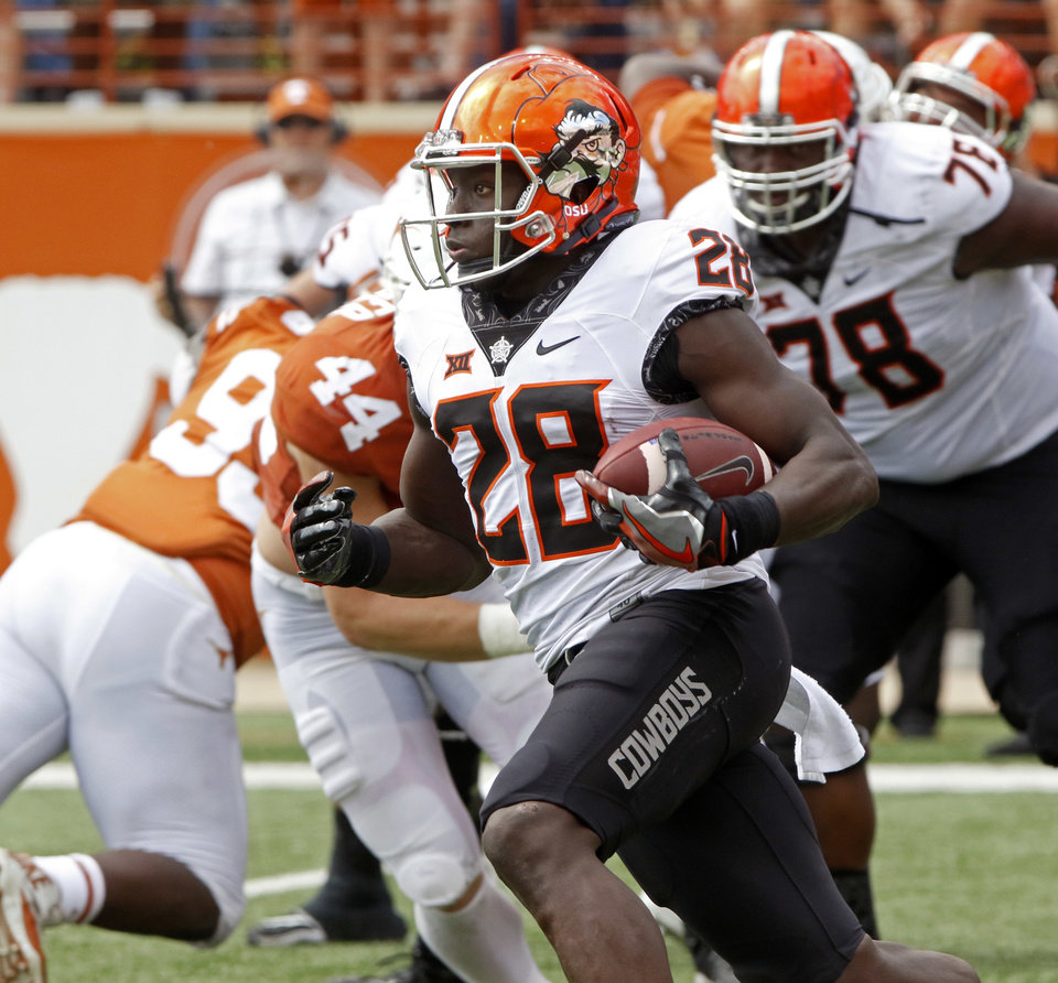 Photo - Oklahoma State receiver James Washington (28) runs the ball during the second half of an NCAA college football game against Texas, Saturday, Oct. 21, 2017, in Austin, Texas. Oklahoma State won 13-10 in overtime. (AP Photo/Michael Thomas)