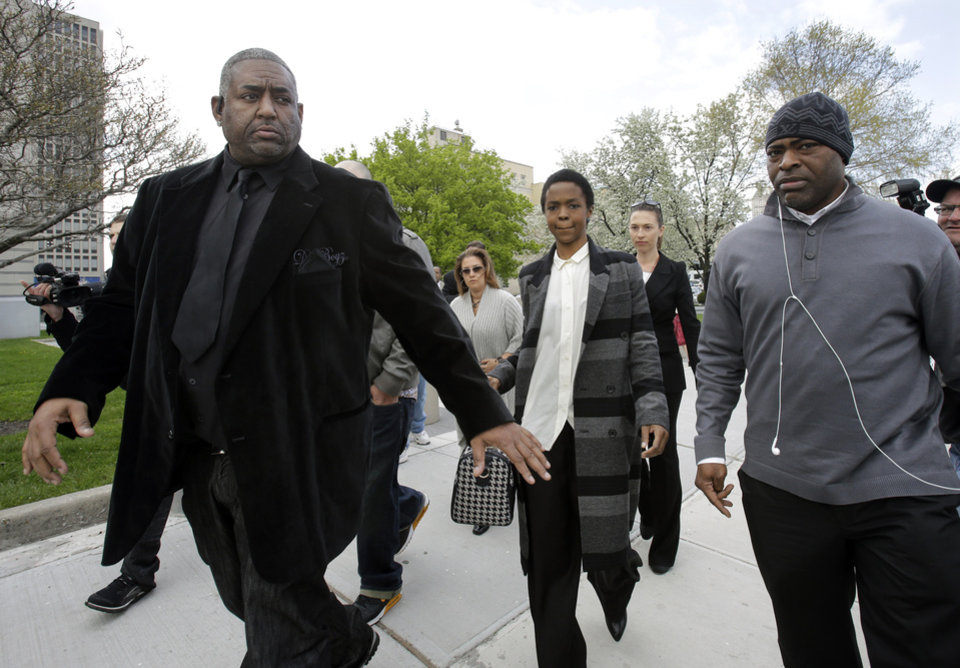Photo - Singer Lauryn Hill, center, walks from federal court in Newark, N.J., Monday, April 22, 2013, after a judge postponed her  tax evasion sentencing and scolded the eight-time Grammy winner for reneging on a promise to make restitution. Hill pleaded guilty last year to not paying federal taxes on $1.8 million earned from 2005 to 2007. At that time, her attorney said she would pay more than $500,000 by the time of her sentencing. It was revealed Monday in court that Hill has paid $50,000. The South Orange resident got her start with The Fugees and began her solo career in 1998 with the acclaimed album