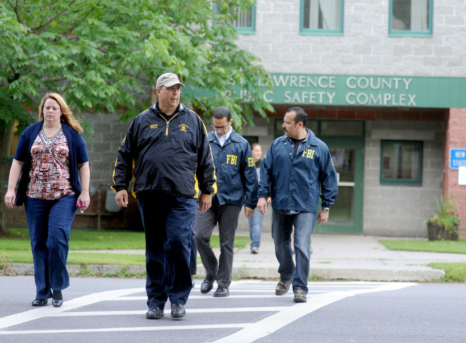 Photo - Mary Rain, left, District Attorney for St. Lawrence County, left, and county Sheriff Kevin M. Wells are followed by a pair of FBI agents while on their way to a news conference Saturday, Aug. 16, 2014 in Canton, N.Y. Wells briefed the media on the arrest of two people in suspected connection with the abduction of two young Amish sisters from their family's roadside vegetable stand on Wednesday, Aug. 13. (AP Photo/Watertown Daily Times, Melanie Kimber Lago) MANDATORY CREDIT, SYRACUSE OUT