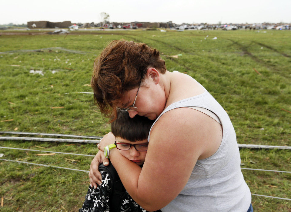 Photo - Rebekah Stuck hugs her son, Aiden Stuck, 7, after she found him in front of the destroyed Briarwood Elementary after a tornado struck south Oklahoma City and Moore, Okla., Monday, May 20, 2013. Aiden Stuck was inside the school when it was hit. Photo by Nate Billings, The Oklahoman