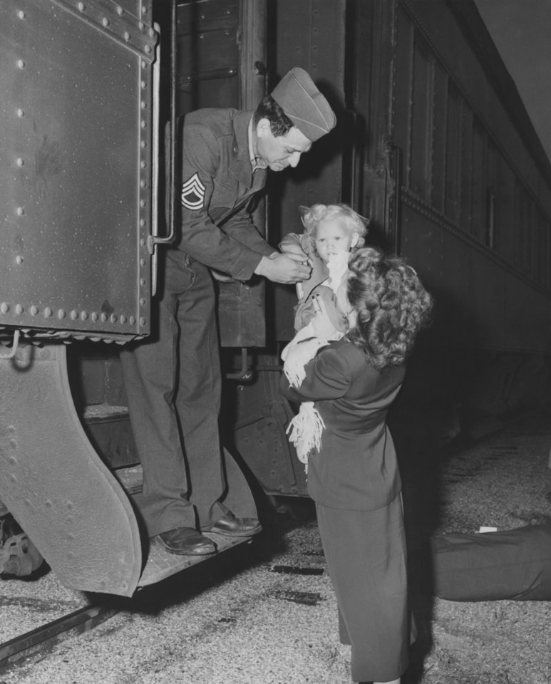 Photo - Home Again to Sill!  Tears and Laughter Mixed as Fist of 45th Tumble Into Loved Ones' Arms.  'Daddy' Is Her Birthday Present.  Thursday was an unusually exciting day in the life of blonde Minnie Leona Woods of Lawton.  Early this morning her mother took her to the railroad station at Fort Sill to greet a near-stranger called 'Daddy' in the person of Sgt. Homer Woods.  Later in the day, Minnie was due to blow out two candles on her birthday cake.  Sgt. Woods timed his arrival perfectly---with the unknowing aid of the army---landing at Sill with other homecoming 45th division Thunderbirds on his daughter's second birthday.  His wife, Violet is shown helping the sergeant get a hug from his youngster.  Photographer and original date unknown.  Published in The Oklahoma City Times 04/17/1952.