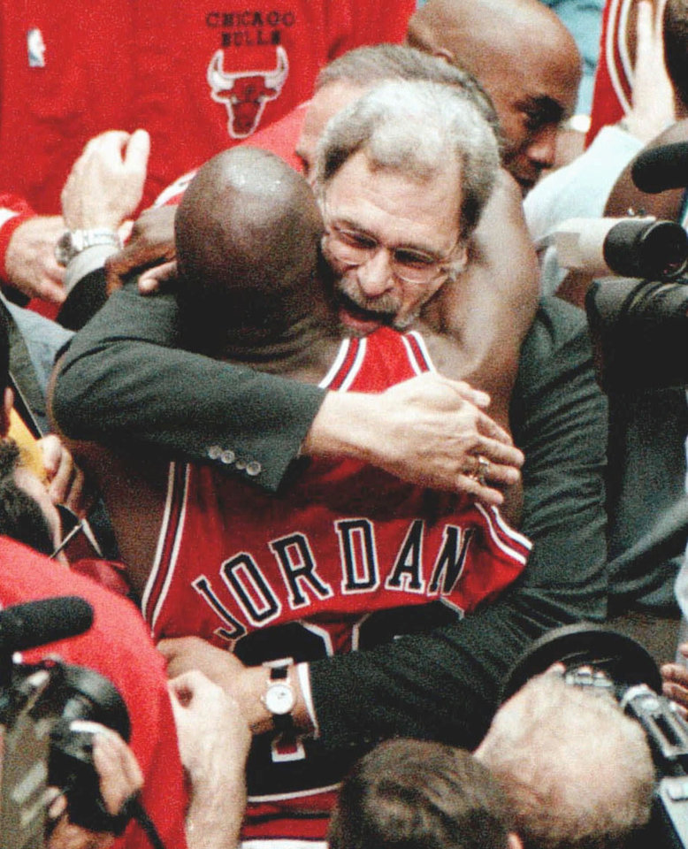 Photo - Chicago Bulls coach Phil Jackson and Michael Jordan embrace after the Bulls won their 6th NBA BASKETBALL championship with an 87-86 win over the Utah Jazz in Game 6 on Sunday, June 14, 1998, at the Delta Center in Salt Lake City. (AP Photo/Chicago Tribune, Nuccio DiNuzzio)
