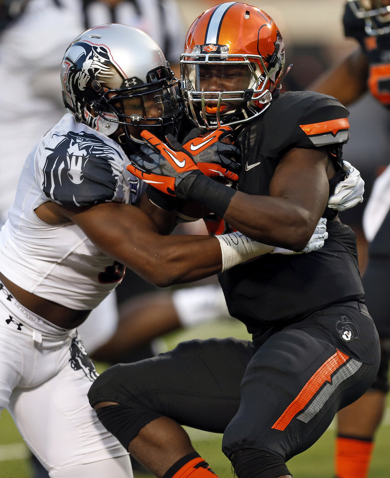 Photo - Texas Tech's Austin Stewart (8) stops Oklahoma State's Desmond Roland (26) at the end of a carry during a college football game between the Oklahoma State Cowboys (OSU) and the Texas Tech Red Raiders at Boone Pickens Stadium in Stillwater, Okla., Thursday, Sept. 25, 2014. Photo by Nate Billings, The Oklahoman