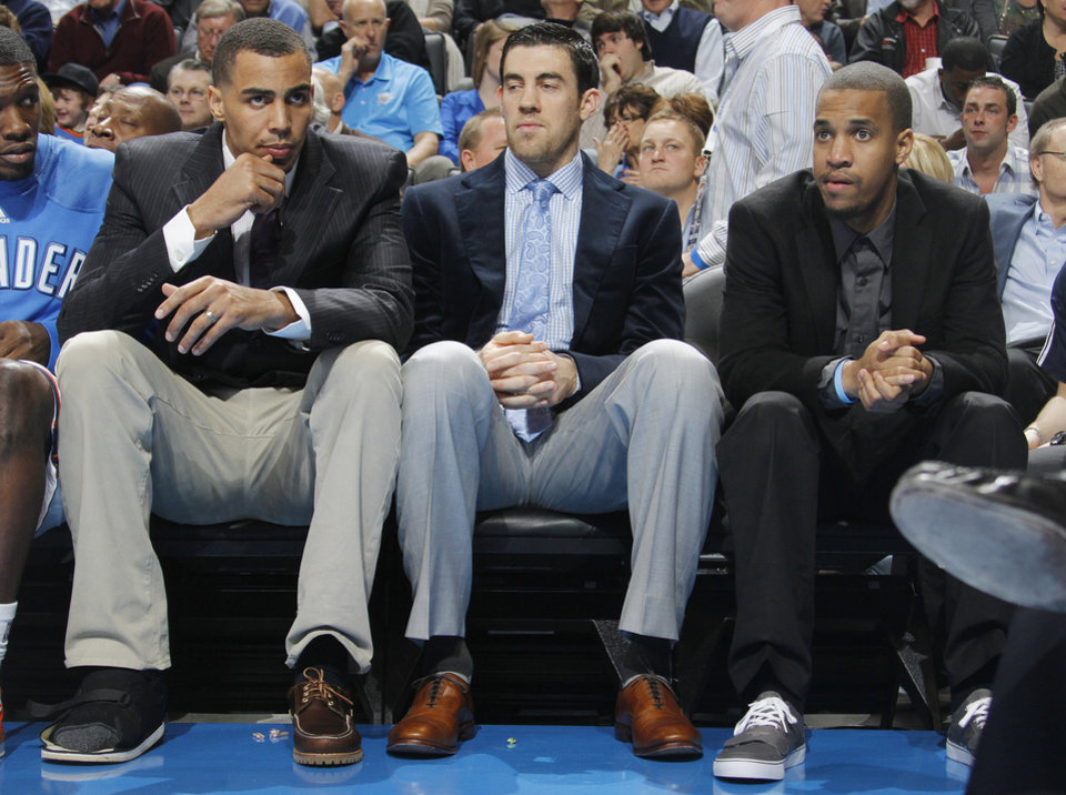 Photo - Oklahoma City's Thabo Sefolosha, Nick Collison and Eric Maynor sit on the bench in street clothes during the NBA basketball game between the Oklahoma City Thunder and the Boston Celtics at the Chesapeake Energy Arena on Wednesday, Feb. 22, 2012 in Oklahoma City, Okla.  Photo by Chris Landsberger, The Oklahoman