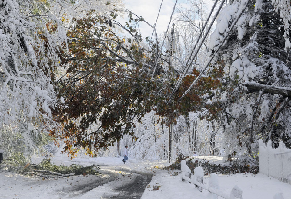 Photo - FILE -- In this Oct. 30, 2011 file photo, a man walks near a tree down on a power line a day after a snow storm in Glastonbury, Conn.  Global warming is rapidly turning America into a stormy and dangerous place, with rising seas and disasters upending lives from flood-stricken Florida to the wildfire-ravaged West, the National Climate Assessment concluded Tuesday, May 6, 2014.  (AP Photo/Jessica Hill, File)