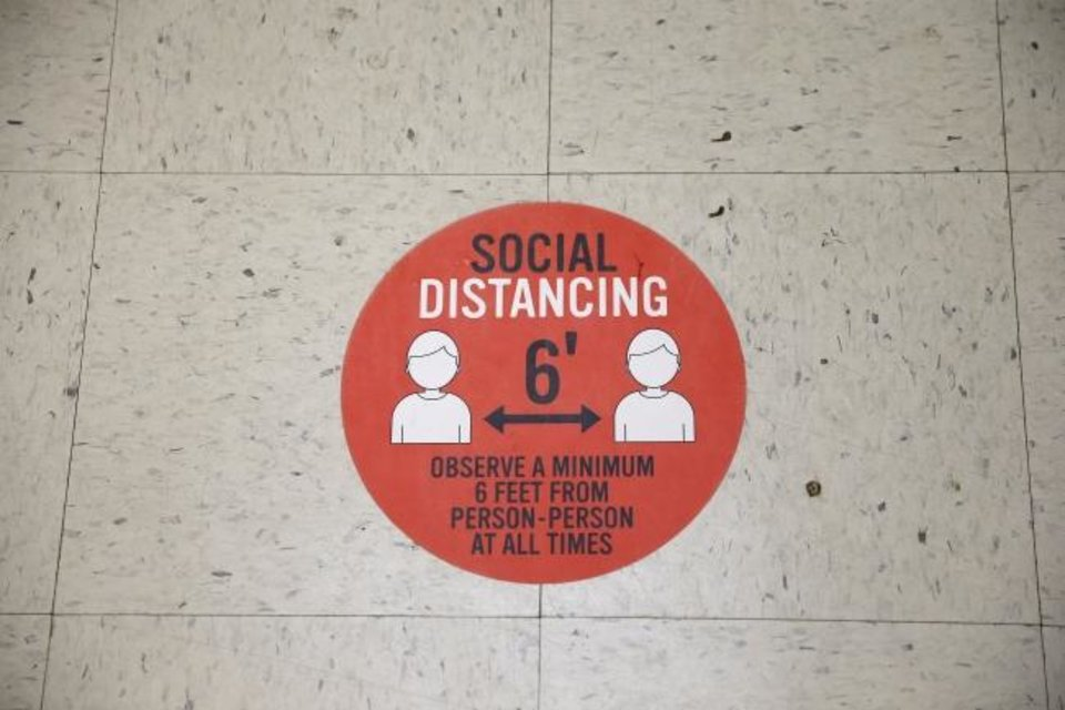 Photo -  A sign on the floor inside the Oklahoma County Election Board reminds voters to practice social distancing during early voting  in Oklahoma City, Friday, June 26, 2020. [Bryan Terry/The Oklahoman]