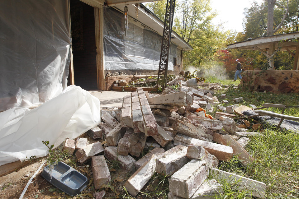 Photo - Chad Devereaux works to clear up bricks that fell from three sides of his in-laws' home in Sparks, Okla., Sunday, Nov. 6, 2011, after two earthquakes hit the area in less than 24 hours. The weekend earthquakes were among the strongest yet in a state that has seen a dramatic, unexplained increase in seismic activity. (AP Photo/Sue Ogrocki) ORG XMIT: OKSO115