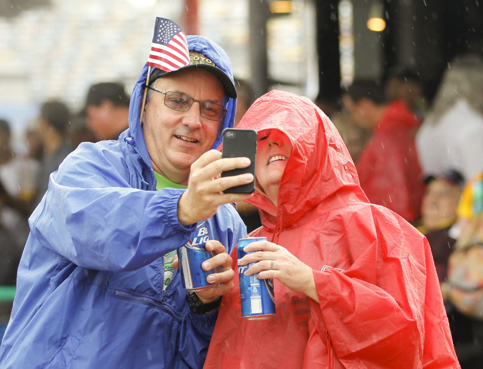 Photo - Race fans make a selfie photo in the Fan Zone during a rain shower before the NASCAR Sprint cup Series auto race at Daytona International Speedway in Daytona Beach, Fla., Saturday, July 5, 2014. (AP Photo/Terry Renna)
