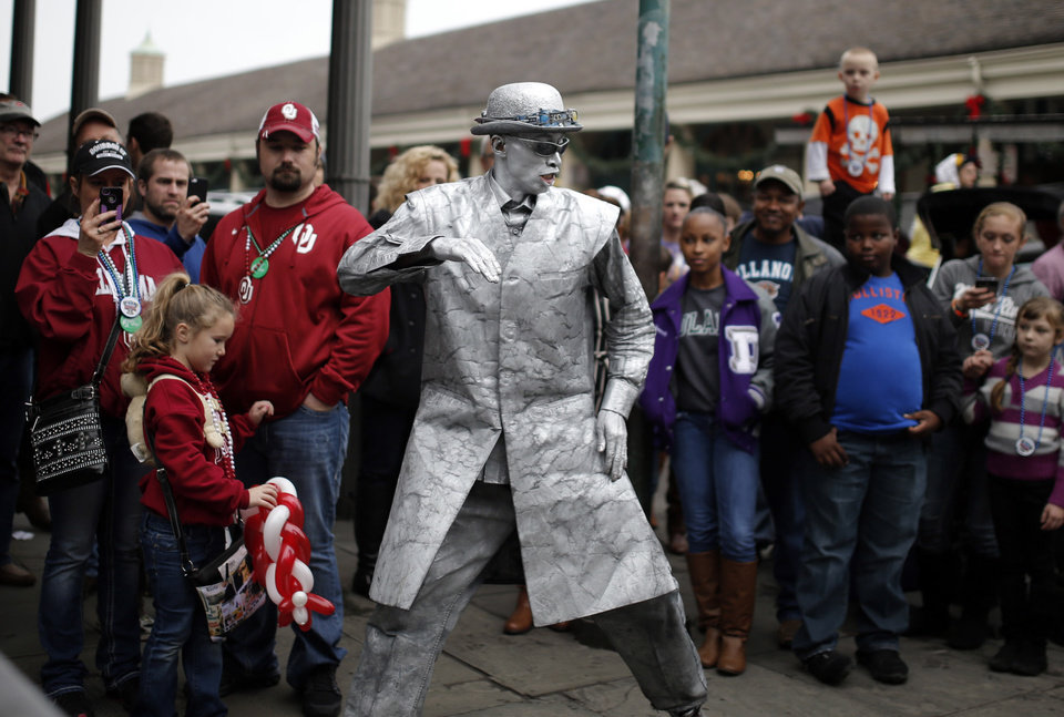 Photo - Oklahoma fans Regina Lorenz, Bobby Lorenz and Kynadie Lorenz, 6, of O'Keene, Okla., watch a street performer in the French Quarter, Wednesday, Jan. 1, 2014 in New Orleans. Photo by Sarah Phipps, The Oklahoman