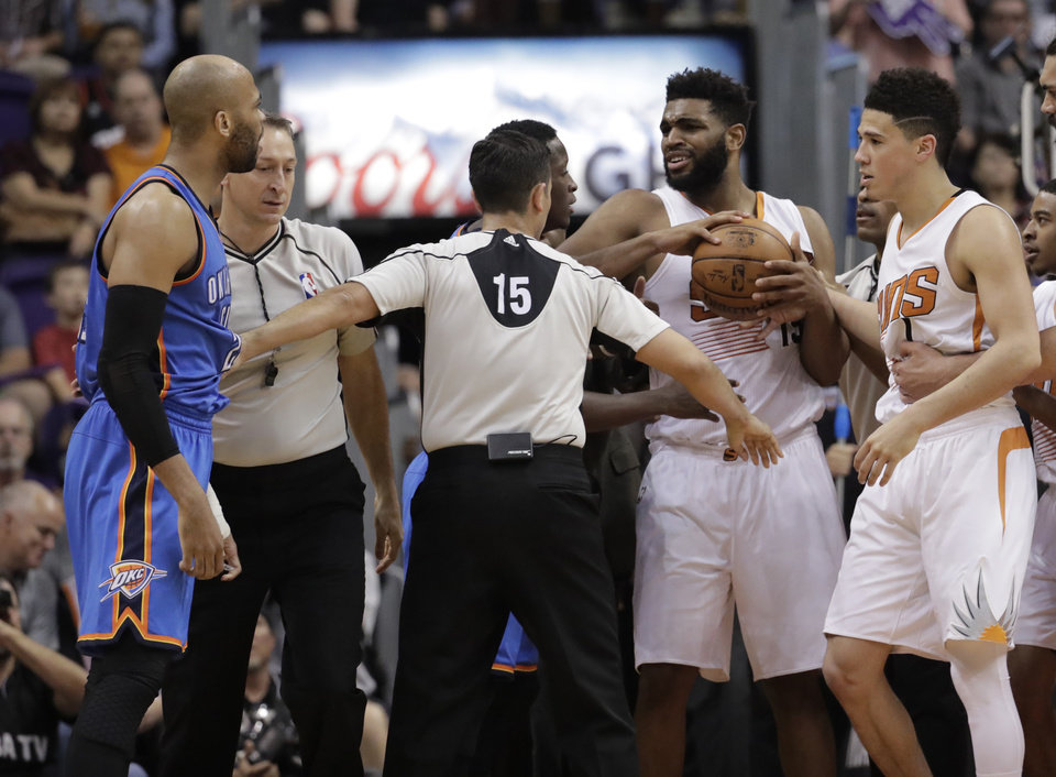 Photo - Phoenix Suns forward Alan Williams, right, and Oklahoma City Thunder forward Taj Gibson, left, are separated by referee Zach Zarba (15) during the second half of an NBA basketball game, Friday, April 7, 2017, in Phoenix. Both players received a technical foul. The Suns won 120-99. (AP Photo/Matt York)