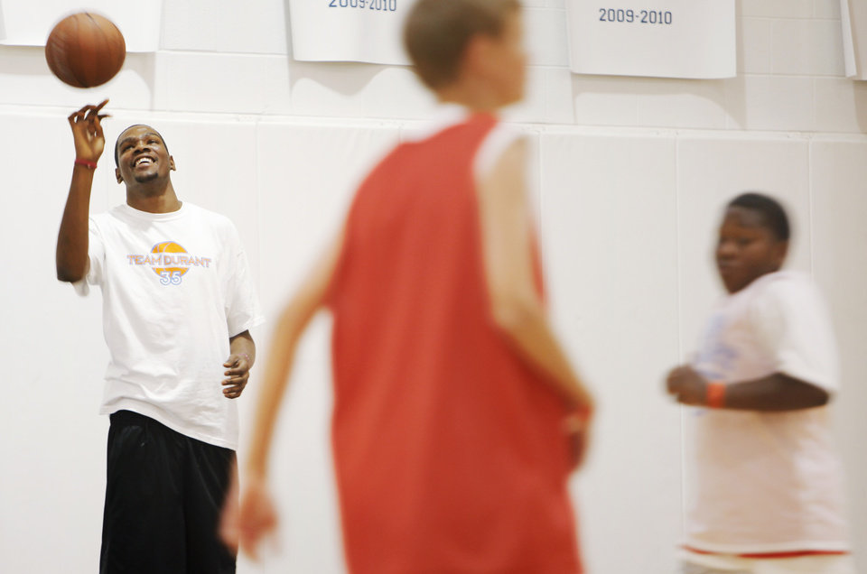 Photo - Kevin Durant, left, spins a basketball as children play during Kevin Durant Basketball Camp on Thursday, July 1, 2010, at Heritage Hall School in Oklahoma City. Photo by Nate Billings, The Oklahoman.