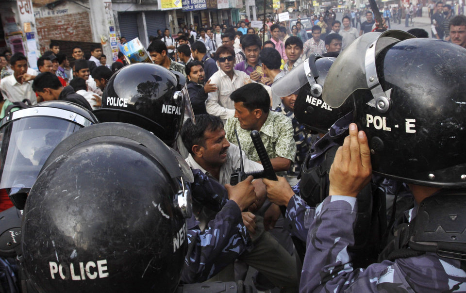 Photo -   Activists of Nepal's opposition parties scuffle with police during a demonstration against Prime Minister Baburam Bhattarai in Katmandu, Nepal, Wednesday, May 30, 2012. The opposition parties said they will team up to topple the government, as they accused the prime minister Wednesday of having no moral or legal grounds to stay in power ahead of new elections. (AP Photo/Binod Joshi)