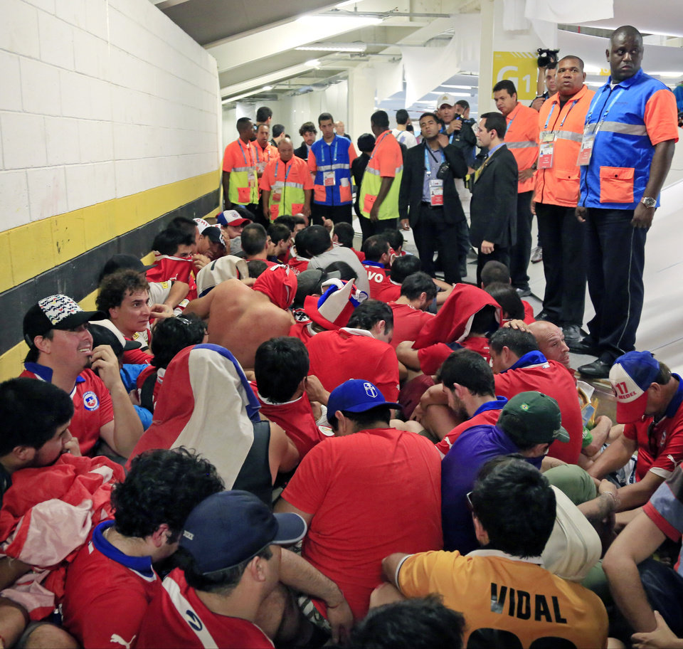 Photo - Chilean fans are surrounded by security personnel after breaking into Maracana Stadium before the group B World Cup soccer match between Spain and Chile in Rio de Janeiro, Brazil, Wednesday, June 18, 2014.  (AP Photo/Bernat Armangue)