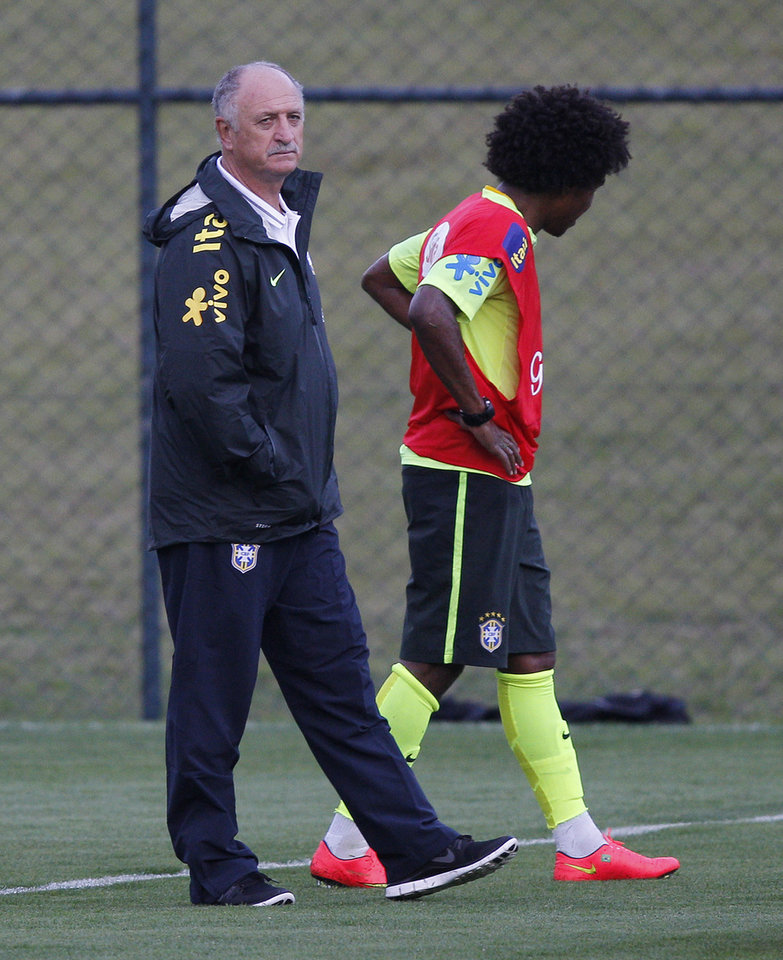 Photo - Brazil's Willian leaves the practice session as head coach Luiz Felipe Scolari walks by his side, at the Granja Comary training center in Teresopolis, Brazil, Saturday, July 5, 2014. Brazil will play in the semifinals of the 2014 Soccer World Cup on Tuesday, July 8. (AP Photo/Leo Correa).