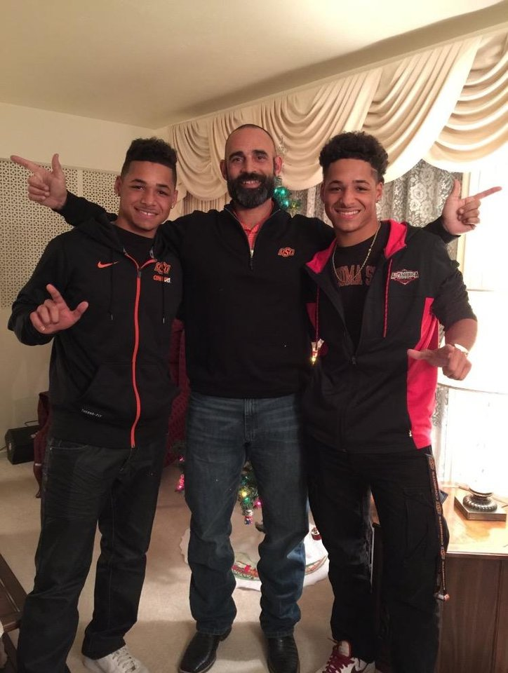 Photo -  Oklahoma State commits Tracin and Tylan Wallace pose for a photo with Cowboy receivers coach Kasey Dunn during an in-home recruiting visit in December. Courtesy Photo.