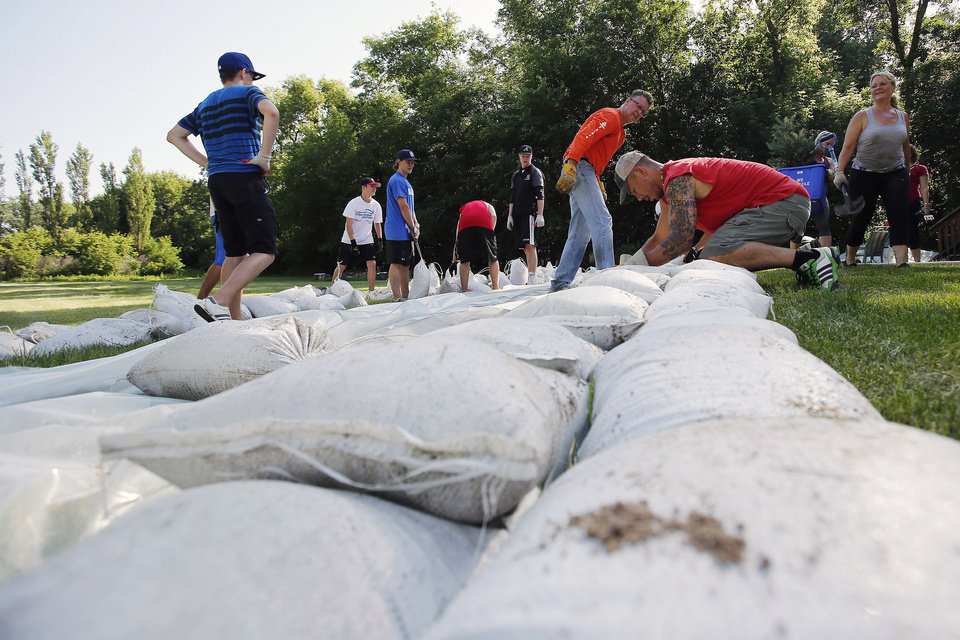 Photo - Friends and family build a sandbag dike in St Francois Xavier, Manitoba, Saturday, July 5, 2014. Tropical storm Arthur hit Canada's Maritime provinces with near-hurricane strength winds and torrential rains, knocking out power to nearly 200,000 customers. (AP Photo/The Canadian Press, John Woods)