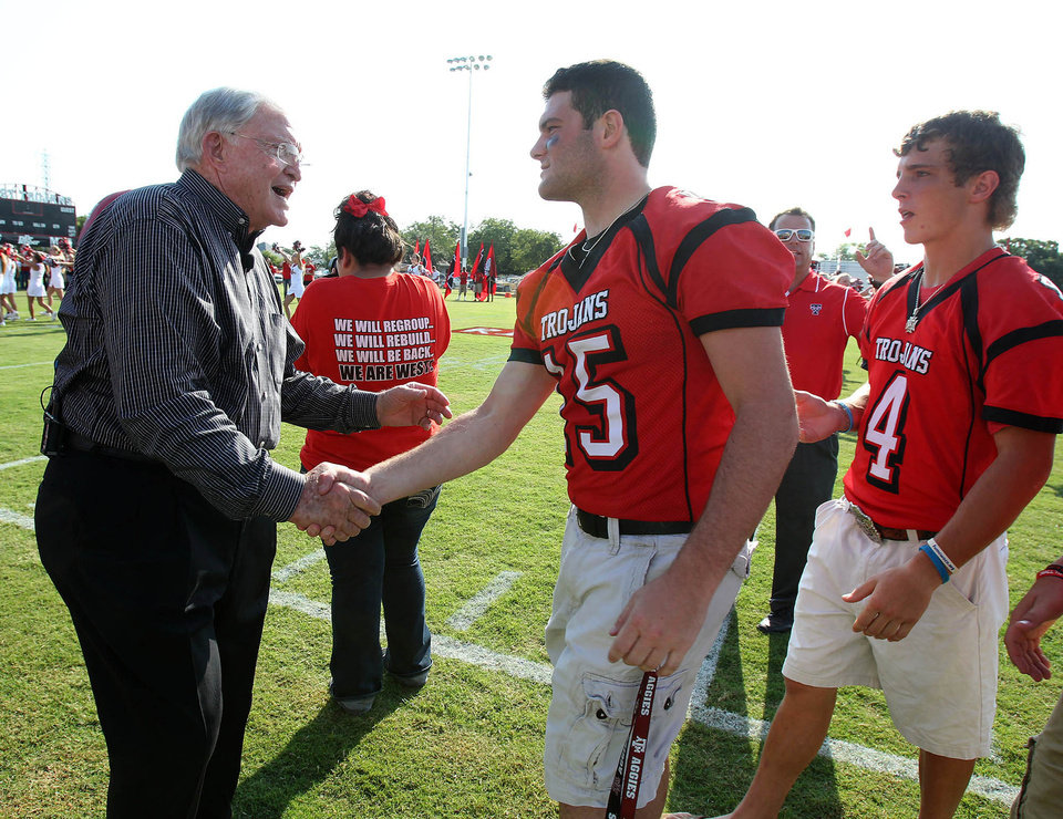 Former Baylor football coach Grant Teaff greets West Trojans football player Tyler Pustejovsky and his teammates on Thursday, Aug.  29, 2013, at a morning pep rally in West, Texas.  The West Trojans open the season Thursday night on their field that was used as a triage site when West Fertilizer Plant exploded on April 17, where 15 people died. (AP Photo/ Waco Tribune Herald, Jerry Larson)