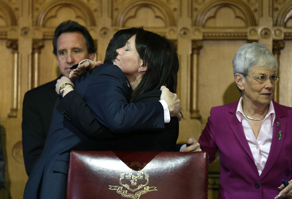 Photo - Connecticut Gov. Dannel P. Malloy, center left, hugs Nicole Hockley, center right, mother of Sandy Hook School shooting victim Dylan Hockley, as Neil Heslin, behind left, father of Sandy Hook shooting victim Jesse Lewis, and Conn. Lt. Gov. Nancy Wyman, right, look on at the conclusion of legislation signing ceremonies at the Capitol in Hartford, Conn., Thursday, April 4, 2013. The legislation signed by Malloy adds more than 100 firearms to the state's assault weapons ban, sets eligibility rules for buying ammunition, and creates what officials have called the nation's first dangerous weapon offender registry. (AP Photo/Steven Senne)