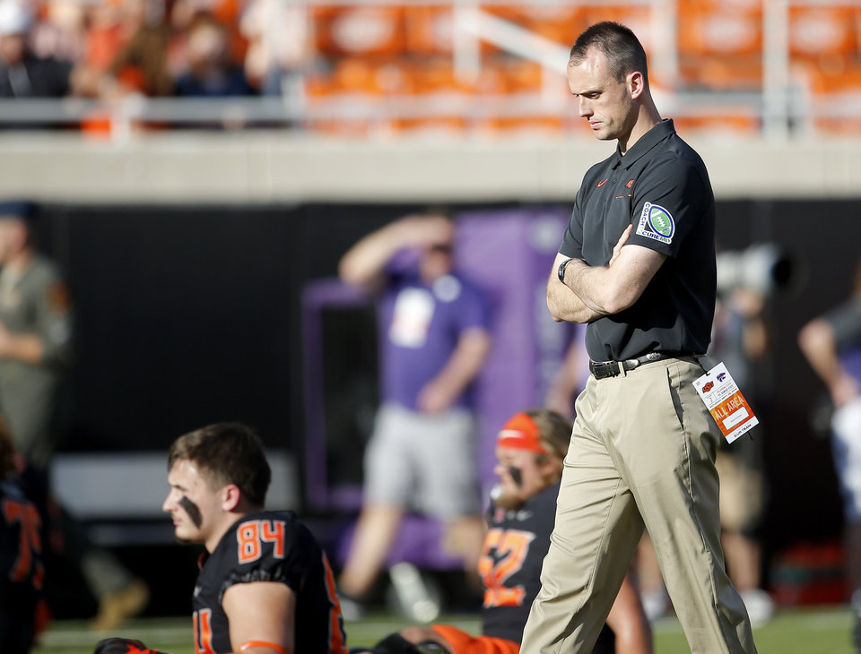 Photo - OSU's Sean Gleeson, Offensive Coordinator / Quarterback, watches players stretch before the college football game between the Oklahoma State Cowboys and the Kansas State Wildcats at Boone Pickens Stadium in Stillwater, Okla., Friday, Sept. 27, 2019. [Sarah Phipps/The Oklahoman]