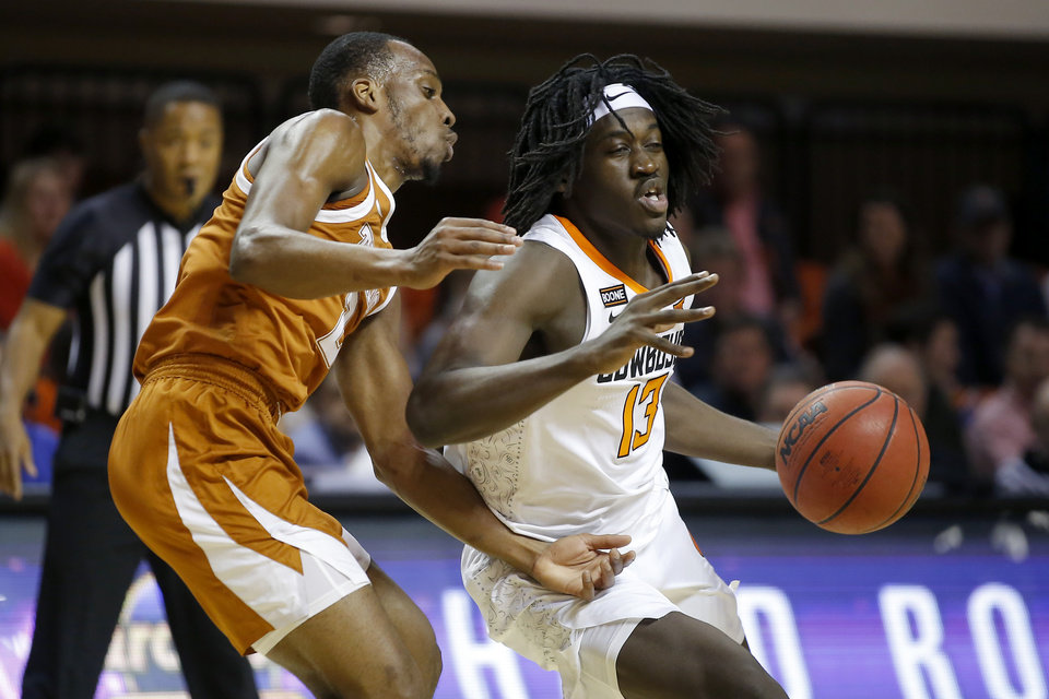 Photo - Oklahoma State's Isaac Likekele (13) goes past Texas' Matt Coleman III (2) during an NCAA basketball game between the Oklahoma State University Cowboys (OSU) and the Texas Longhorns at Gallagher-Iba Arena in Stillwater, Okla., Wednesday, Jan. 15, 2020. [Bryan Terry/The Oklahoman]