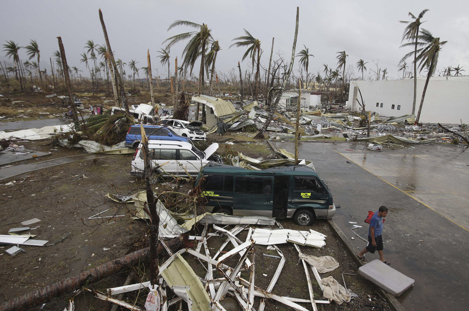 Photo - A survivor passes by damaged vehicles and houses at typhoon ravaged Tacloban city, Leyte province, central Philippines on Tuesday, Nov. 12, 2013. The Philippines emerged as a rising economic star in Asia but the trail of death and destruction left by Typhoon Haiyan has highlighted a key weakness: fragile infrastructure resulting from decades of neglect and corruption. (AP Photo/Aaron Favila)