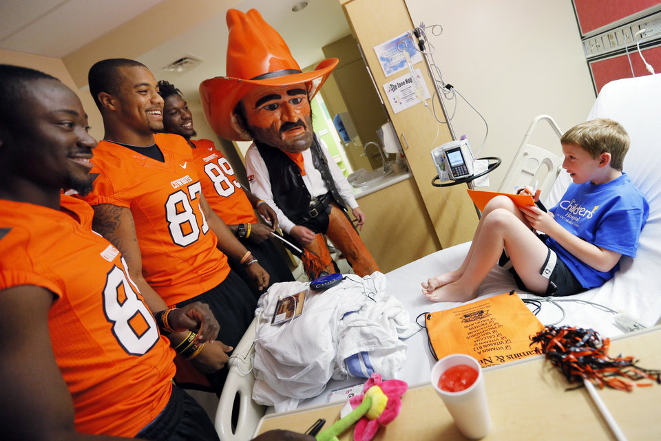 From left, Oklahoma State\'s Nick Rockwell, Tracy Moore, Nigel Nicholas and mascot Pistol Pete visit Ernest Cobb, 9, during a visit by OSU football players to The Children\'s Hospital in Oklahoma City, Wednesday, July 11, 2012. Cobb is a patient at The Children\'s Hospital. Photo by Nate Billings, The Oklahoman