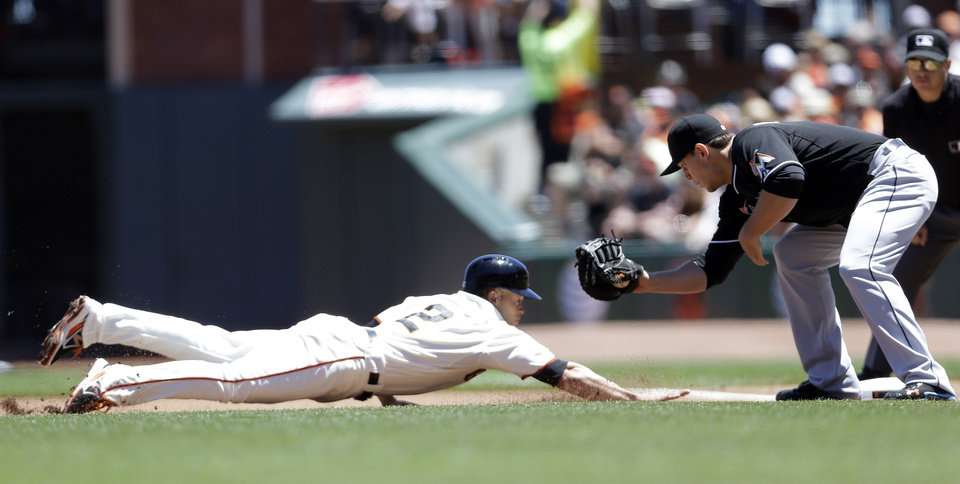 Photo - San Francisco Giants' Juan Perez is picked off at first base by Miami Marlins first baseman Logan Morrison during the second inning of a baseball game on Saturday, June 22, 2013, in San Francisco. (AP Photo/Marcio Jose Sanchez)