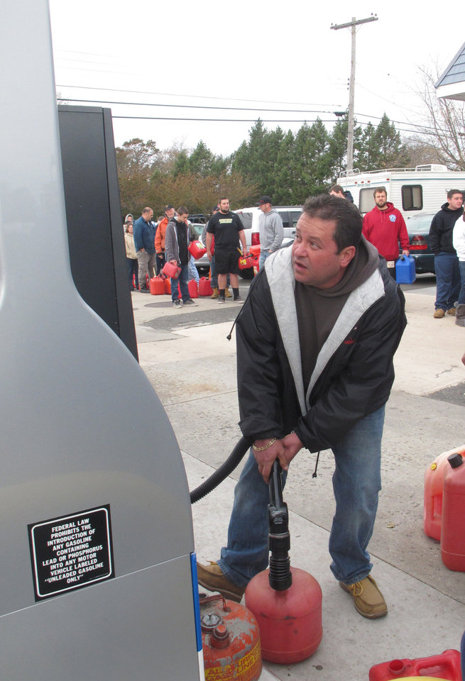 A man fills a gas tank at a gas station in Point Pleasant N.J. on Thursday, Nov. 1, 2012. was one of the few in the shore region that was selling gasoline on Nov. 1, 2012. Motorists in the New York City area and across New Jersey are facing a second day of enormous gas lines at those stations that still have both electricity and supplies. (AP Photo/Wayne Parry)