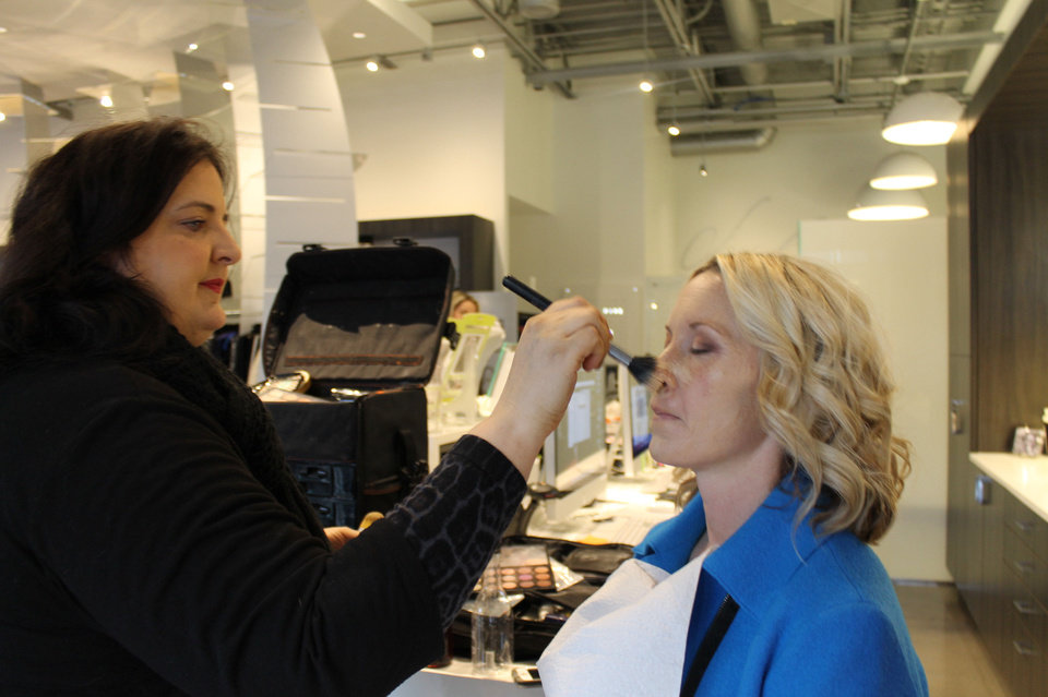 Photo - Sharon Tabb applies makeup to Christa Gray as part of her