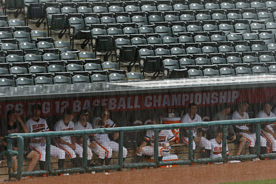Photo - The Oklahoma State team waits in the dugout during a rain delay in a Big 12 Tournament baseball game between Oklahoma State University and the University of Texas at Chickasaw Bricktown Ballpark in Oklahoma City, Saturday, May 24, 2014. Photo by Bryan Terry The Oklahoman