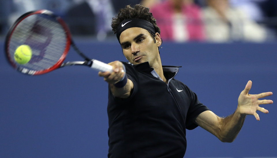 Photo - Roger Federer, of Switzerland, returns to Gael Monfils, of France, during the quarterfinals of the U.S. Open tennis tournament, Thursday, Sept. 4, 2014, in New York. (AP Photo/Charles Krupa)